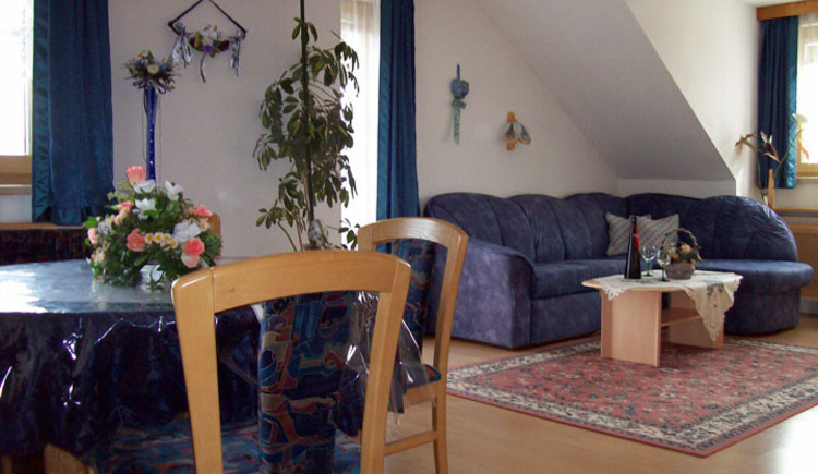 Living area with a sofa and a small table, as well as a Dining possibility with a table and chairs.