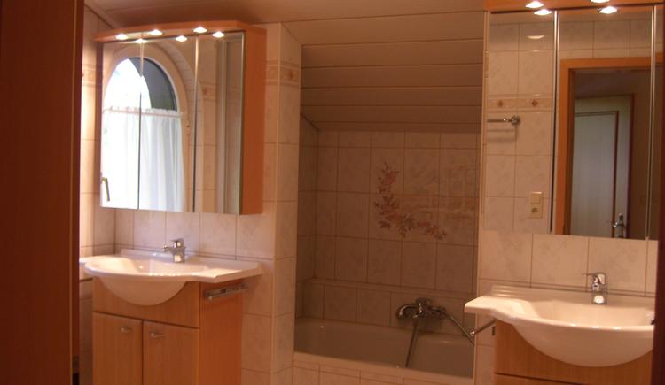 Waschbecken, im Hintergrund eine Badewanne