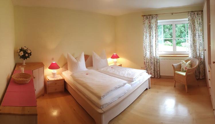 Doppelbett, Nachtkästchen, seitlich eine Kommode, im Hintergrund ein Fenster, Stuhl