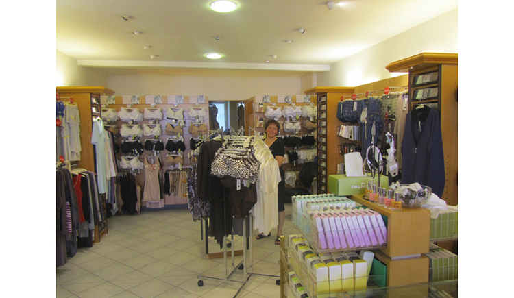 Shop from inside, clothes rack, wall clothes, in the background a person