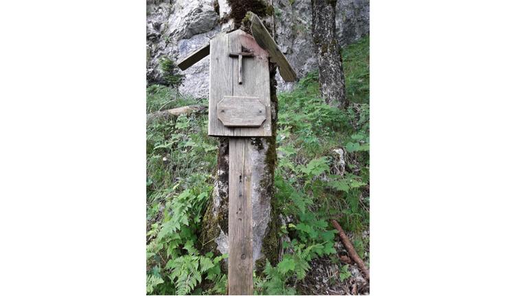 Blick auf ein Holzmarterl im Wald
