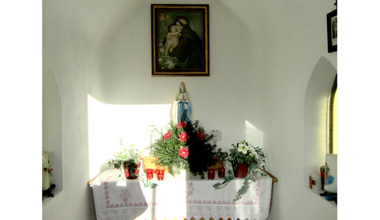 Blick auf den Altar mit Blumen, Kerzen, Heiligenfigur