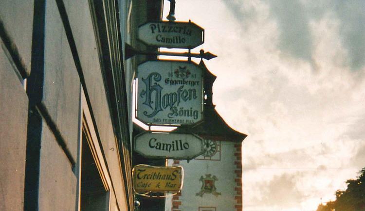 Außenansicht der Pizzeria Camillo mit Marktturm im Hintergrund