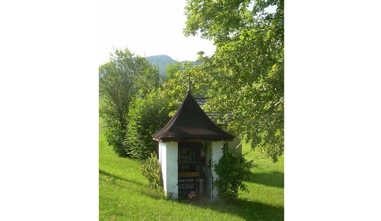 Blick auf eine Kapelle in einer Wiese, seitlich Bäume