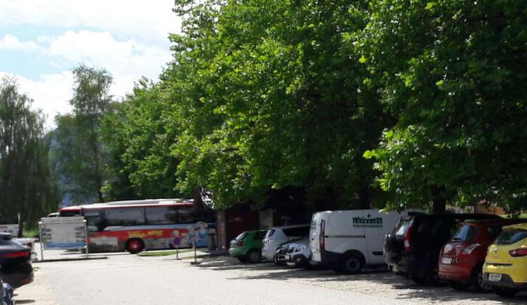 hinter den parkenden Autos seitlich befindet sich eine kleine öffentliche Toilette, Bäume