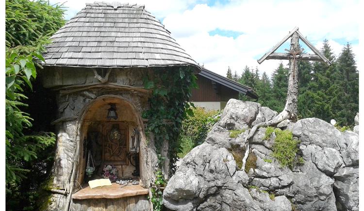 Blick auf eine Grotte in einem Baumstamm, seitlich Steine und ein Holzkreuz
