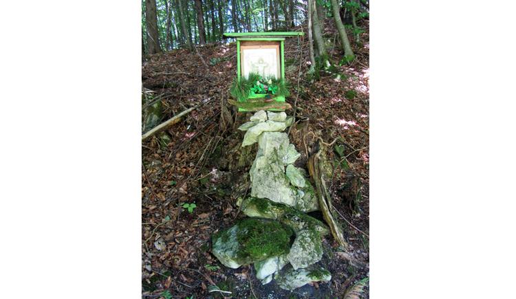 Blick auf eine Gedenktafel auf Steinen, im Hintergrund Wald