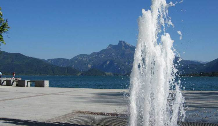 Blick auf den See, im Hintergrund der Schafberg, im Vordergrund ein Springbrunnen. (© www.mondsee.at)