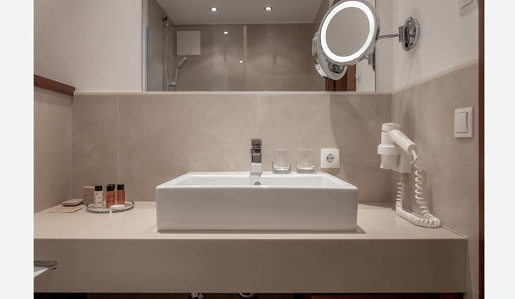 Sink, hairdryer, toiletries in small flasks, cosmetic mirror