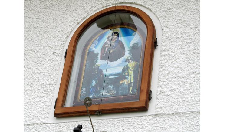 Blick auf ein Bild hinter Glas auf einer Hauswand