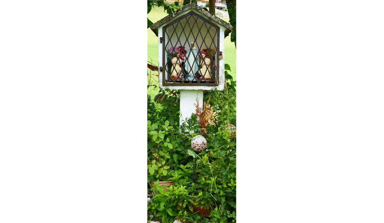 Blick auf den Bildstock, hinter Gitter eine Heiligen Figur, Blumen, im Vordergrund Sträucher