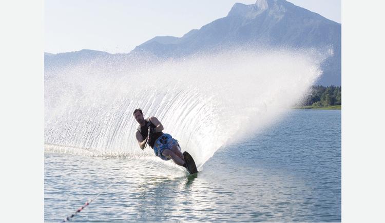 Wasserskifahrer am See. im Hintergrund spritzendes Wasser und die Berge