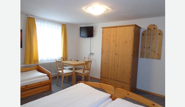 im Vordergrund ein kleiner Teil vom Doppelbett und Einzelbett zu sehen, im Hintergrund seitlich ein Tisch mit Stühlen, Fenster, Fernseher an der Wand, Kleiderschrank