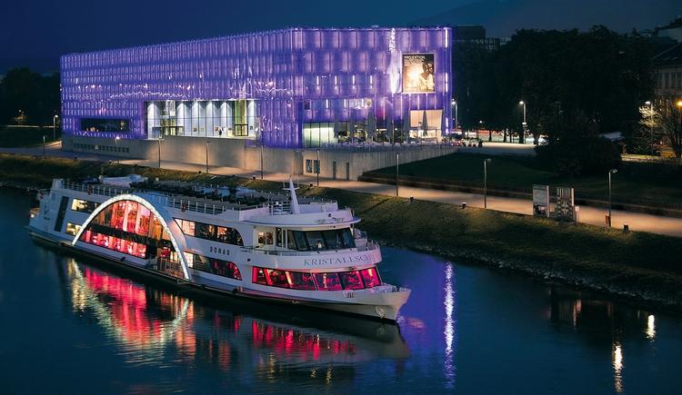 Kristallschiff der Flotte Donauschiffahrt Wurm + Köck vor dem Lentos Kunstmuseum in Linz bei Nacht. (© Donauschiffahrt Wurm + Köck)