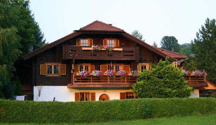 Blick auf das Haus mit Balkon und Blumen, davor eine Hecke