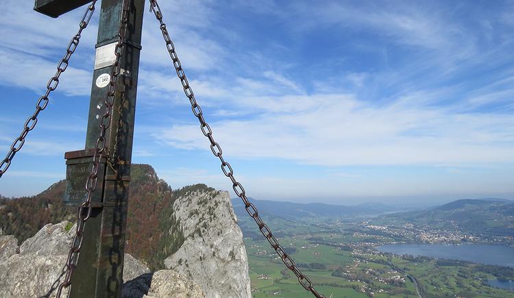 Ausblick vom Gipfel des Almkogels. Links im Bild erkennt man noch das Stahlkreuz, dahinter Blick auf die Drachenwand. Rechts im Bild ein Blick in die Ferne auf den Mondsee und den Ort Mondsee, ganz im Hintergrund ist noch der Irrsee erkennbar.