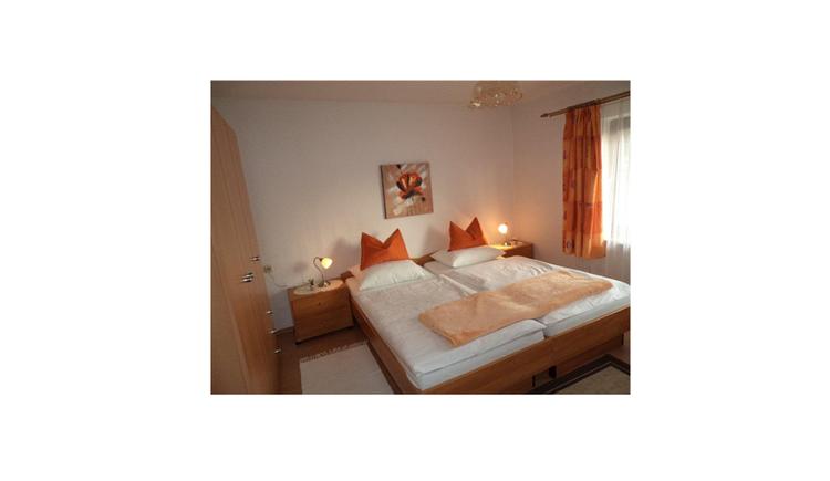 Schlafzimmer mit Doppelbett, Nachtkästchen, Tischlampe, seitlich ein Kleiderschrank, gegenüber ein Fenster