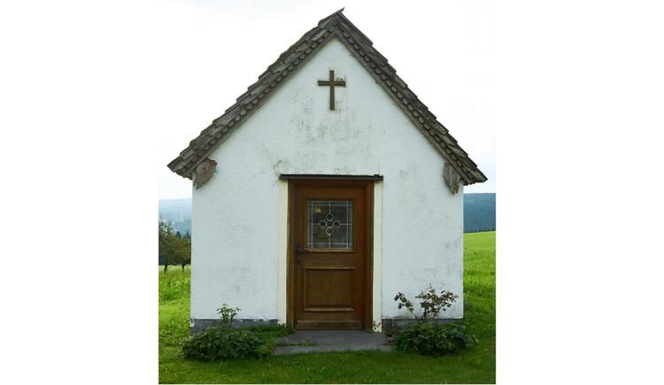 Blick auf die Kapelle, Holztür, Kreuz