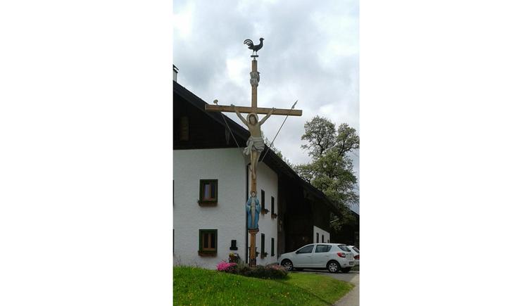 Blick auf ein Kreuz, im Hintergrund parkende Autos, Haus