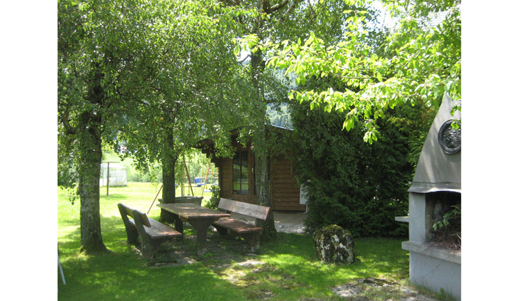 View at the garden with wooden benches and table under the trees, a brick barbecue on the side, a hut in the background. (© Pöllmann)