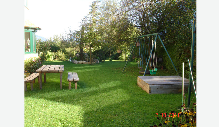 Garden with table and benchens made out of wood and a small play area for children.