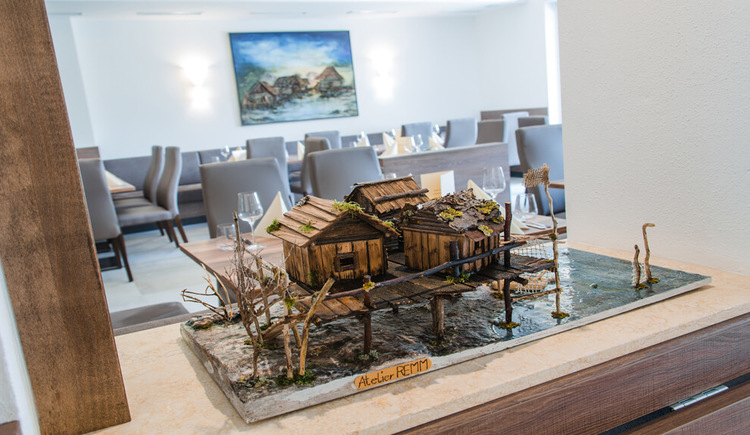 Blick ins Restaurant mit einem Pfahlbaumodell im Vordergrund
