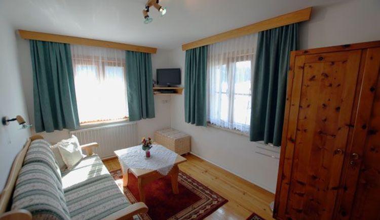 Unser Zimmer Gosaublick hat einen weiteren kleinen Raum mit einer Couch und einem kleinen Tisch für gemütliches Beisammensein. Es bietet auch einen kleinen Fernseher. Die Couch könnte man bei Bedarf auch ausziehen. (© Hedwig Gamsjäger)