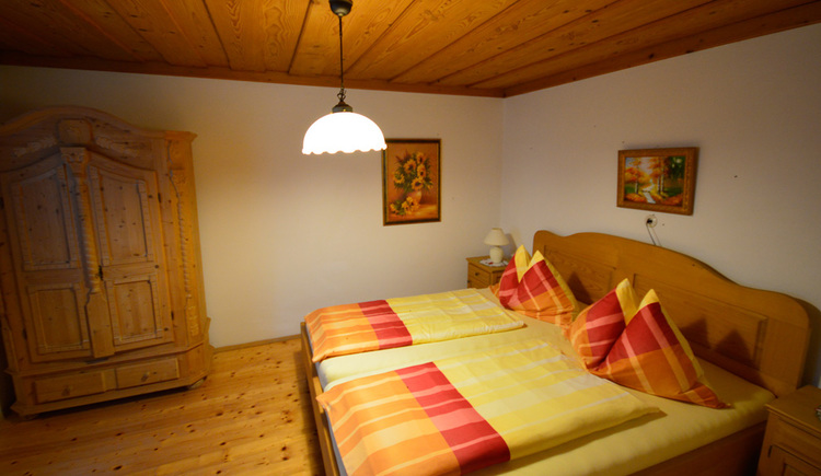 Bedroom with double bed, wardrobe at the back in the picture, wooden floor