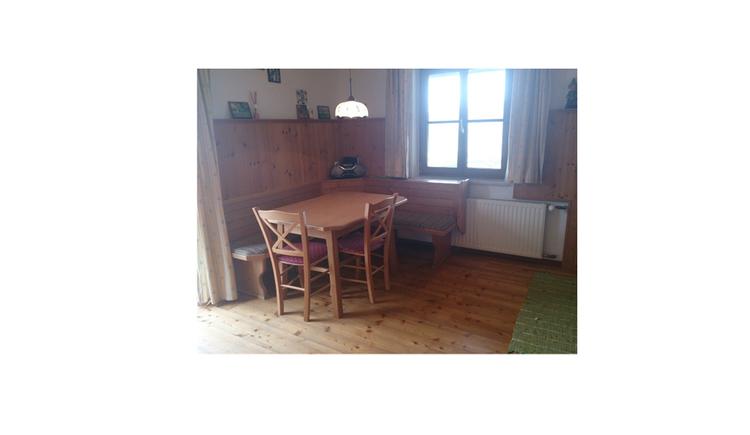 Wohnbereich mit Essecke, Tisch und Stühle, im Hintergrund ein Fenster