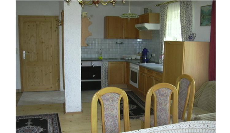 Wohnbereich, im Hintergrund Küche mit Herd, Spüle, Herd, Kaffeemaschine, Fenster, im Vordergrund Stühle