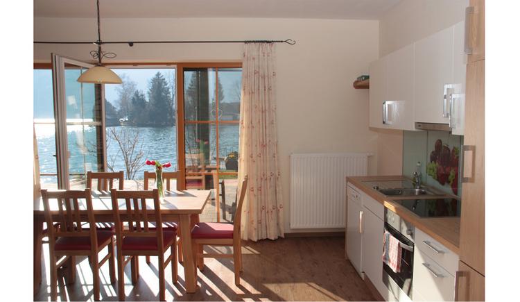 seitlich eine Küche, Tisch mit Stühlen, Ausblick durch die offene Balkontür auf den See