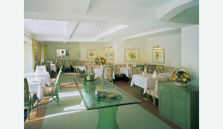 Covered tables with chairs, on the side a chest of drawers with a banquet, pictures on the walls. (© Hotel Seehof)
