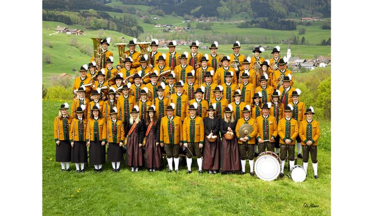Personen stehen in der Wiese, teilweise mit Instrumenten