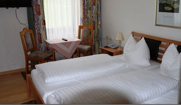 double bed with bedside table, lamp, telephone, in the background is a table with chairs\n