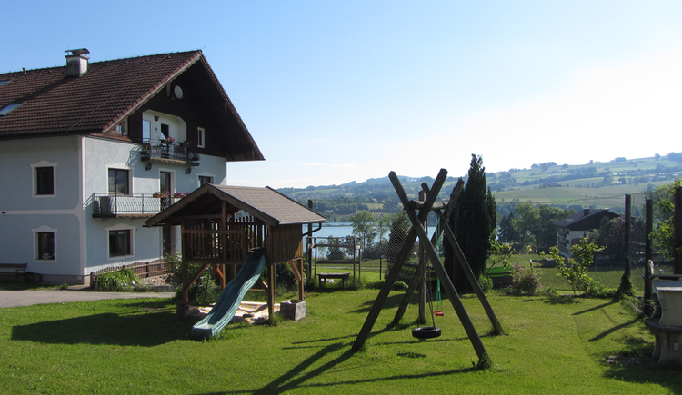 Look at the farmhouse with the playground in front. Slide, tire swing, sandbox and playhouse made out of wood. In the background the lake is visible.