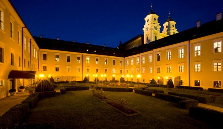 Blick auf das Schloss Mondsee bei Nacht, im Hintergrund die Türme von der Kirche - Basilika St. Michael, im Vordergrund der Schlossgarten mit dem Springbrunnen. (© Schloss Mondsee)