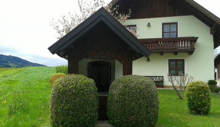 Blick auf eine Kapelle, im Hintergrund ein Haus, umgeben von Wiesen