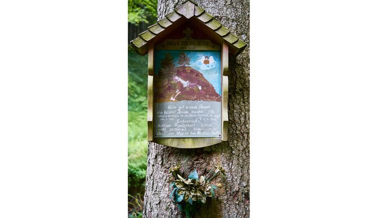 Blick auf das Holzmarterl mit einem Bild, Text, auf einem Baum, im Hintergrund ein Wald