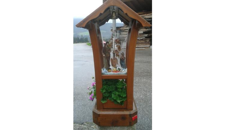 Blick auf den Holz-Bildstock mit Heiligenfiguren hinter Glas, darunter Blumen