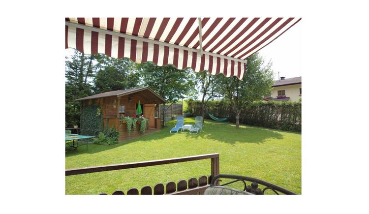 Blick in der Garten, mit Gartenhütte aus Holz, Liegestühle, im Hintergrund Hängematte, Hecke