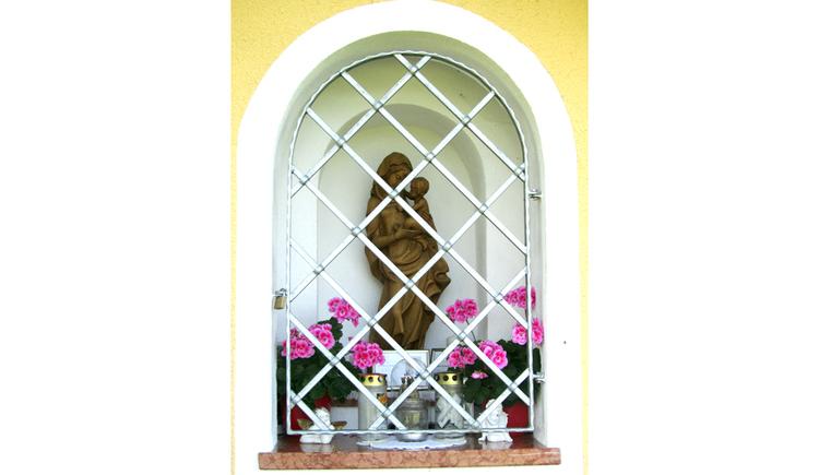 Blick auf eine Heiligenstatue hinter Gittern, Blumen