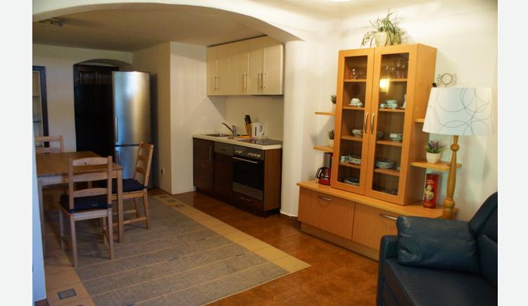 Wohnbereich mit Couch, Stehlampe, Kommode, kleine Kochecke mit Herd, Wasserkocher, Kühlschrank, Tisch und Stühle