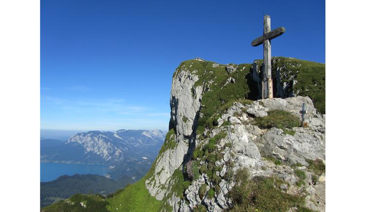 Blick auf ein Kreuz am Gipfel eines Berges, im Hintergrund seitlich der See