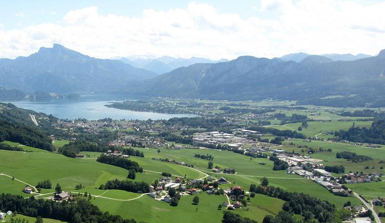 Vom Hubschrauber aus nördlicher Richtung über Ort und See Mondsee fotografiert, umrahmt vom Panorama bestehend aus Schafberg und Drachenwandmassiv.