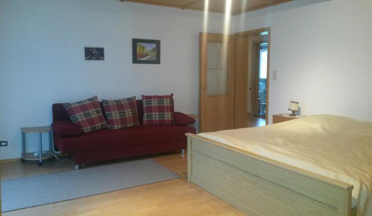 Doppelbett, Couch, seitlich eine offene Tür