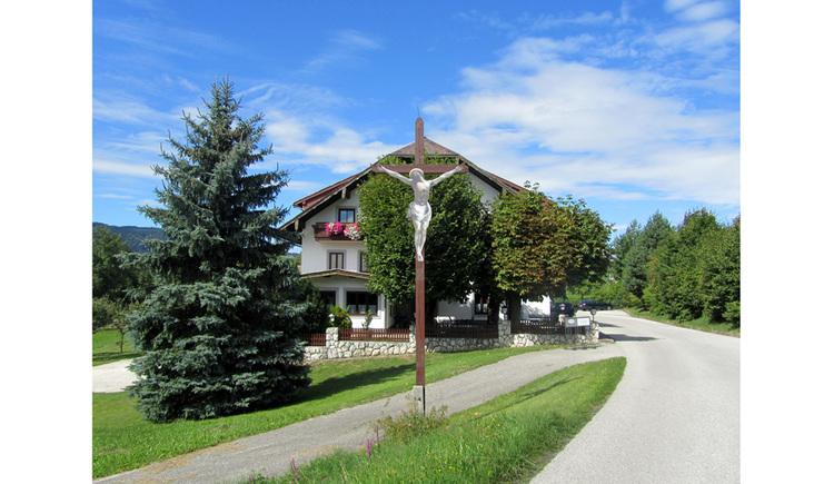 Blick auf ein Holzkreuz, seitlich Straßen, Bäume, im Hintergrund ein Haus