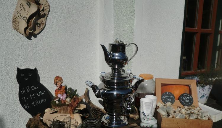 Silberne Teekanne in der Mitte des Fotos mit Zubehör und Zutaten