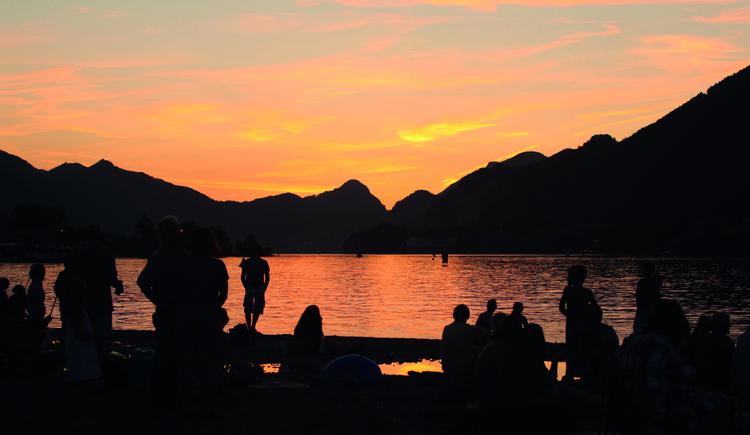 Eine Gruppe Menschen am Ufer des Wolfgangsee, die Abendstimmung genießend. (© WTG)