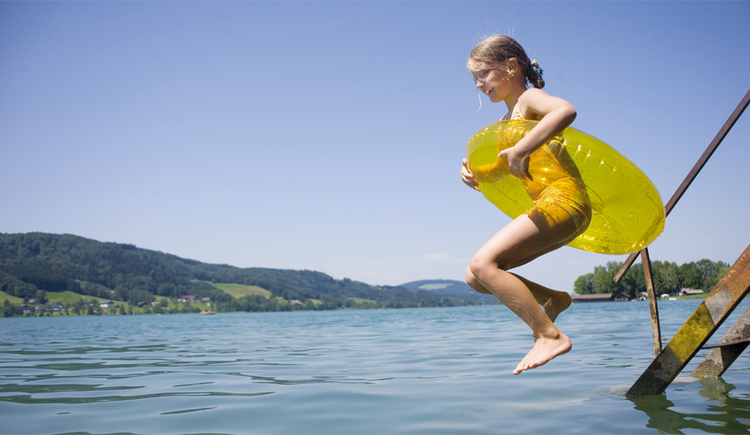 A girl is jumping into the lake with a tube. (© Tourismusverband MondSeeLand)