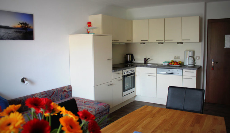 kitchen with stove, water cooker, sink, dishwasher, coffee machine, in the foreground a table with a chair, couch